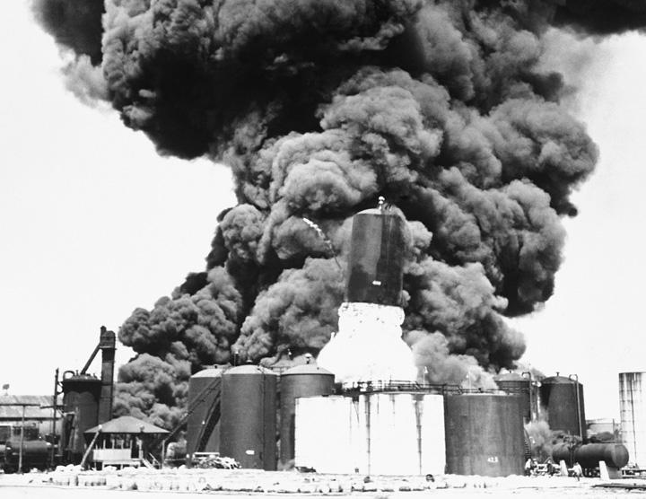 Dette helt specielle foto fra 1949 viser det øjeblik, hvor et indre overtryk fik en tank til at skyde 15 meter i vejret og tømme sit indhold af 160 tons brændende asfalt ud af åbningen i bunden. Der strømmer også brændende asfalt ud af et overrevet rør til venstre for tanken. Bemærk de flygtende mennesker nederst til højre i billedet. Foto: APImages/Polfoto.